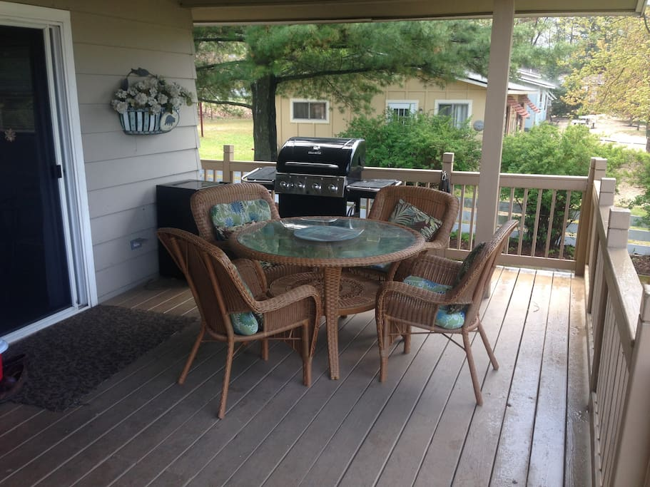 Table set on deck, gas grill.
