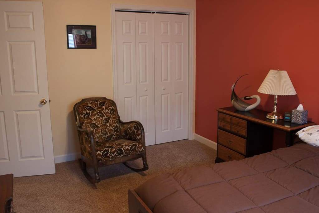 Rocking chair and closet in bedroom