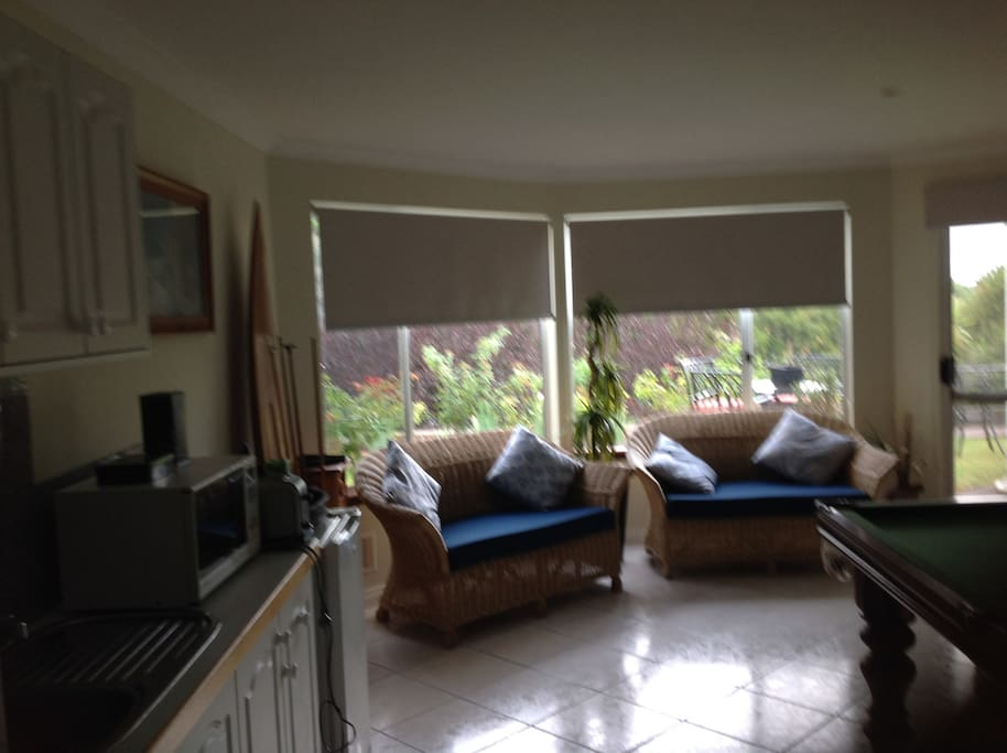 Spacious family room with dining table 6 chairs and bar fridge  microwave and kitchenette.