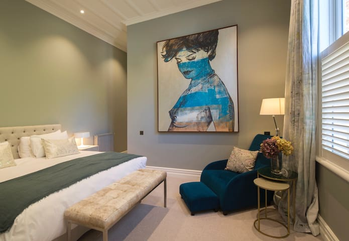 Bedroom three has a super king bed, gorgeous art work and a teal velvet reading chair