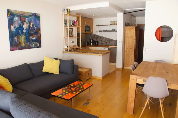 open living space with kitchen area and dinner table. The sofa contains a fold out bed.