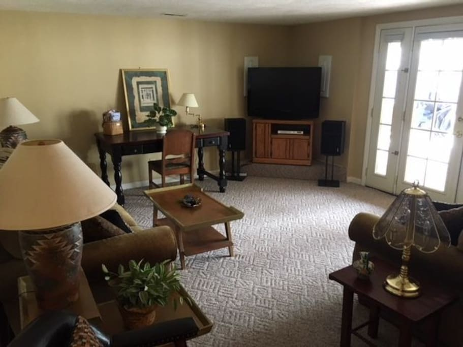 Lower level living room w/ couch, love seat, desk, flat screen TV w/ satellite and DVR/VHS, french doors to patio