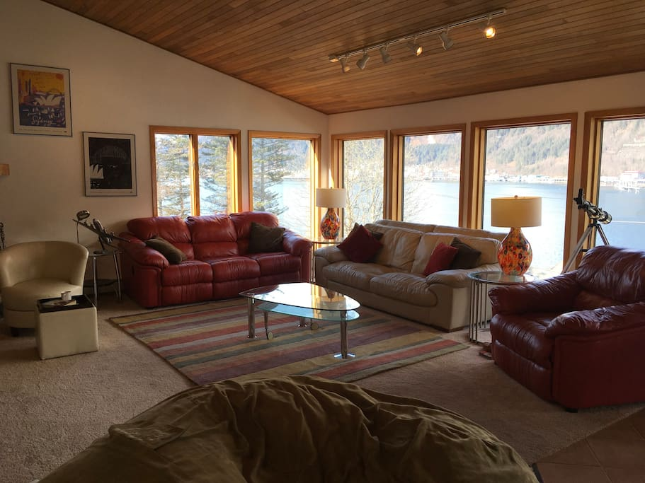 the living room with floor to ceiling windows overlooking the channel