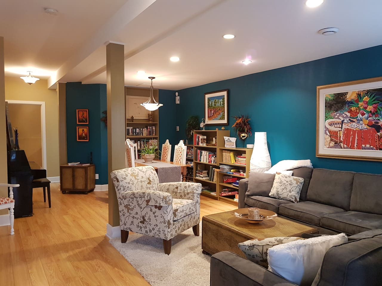 Living room with sectional couch and dining area. Bookshelves contain books, games, and puzzles.