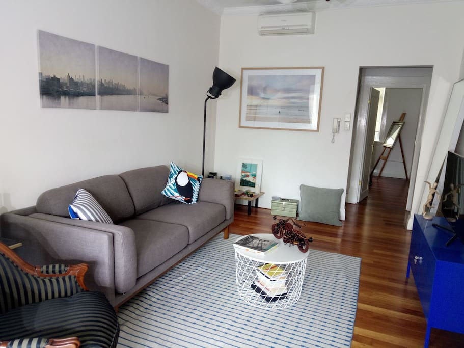 Bright living room, super comfy sofa from West Elm, design / architecture books to read, travel info on Sydney, A/C and ceiling fan, artwork on the walls,