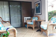 Front lanai with bright, warm morning sunshine facing the ocean, with comfy tropical furnishings