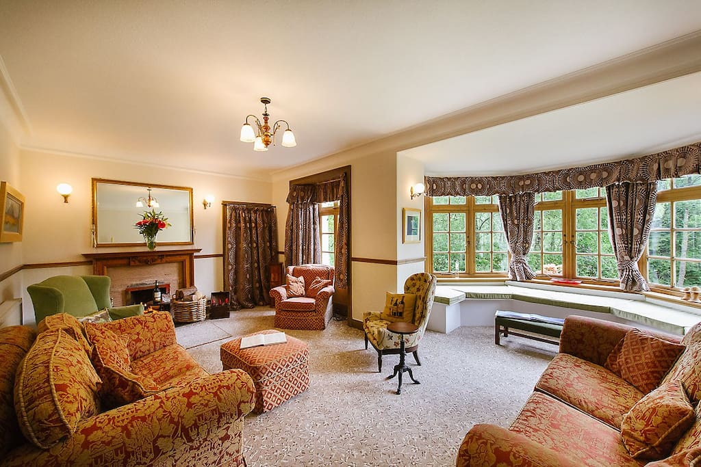 Portnellan House drawing room with large bay window and open fire