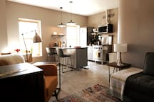 Kitchen and living room from entrance door. The kitchen has two counter stools for you to eat breakfast, lunch, dinner and quick snacks at.