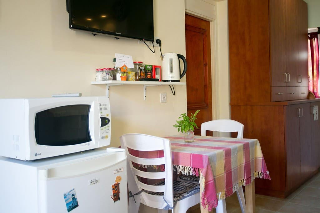 Refrigerator, microwave, electric kettle, dining table and television.