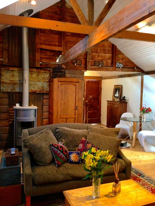 A large open plan living space with vaulted ceilings and exposed beams makes this cottage feel spacious while a beautiful Danish wood burning stove makes for a very cozy visit!