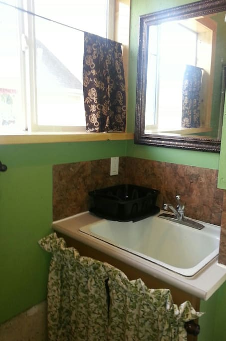 In front of the shower - very deep cast iron sink, dish rack, dish pan, dish soap, scrubbers and tea/dish towels are provided.  Large Mirror with Wall plug ins for your essential morning electrical devices.