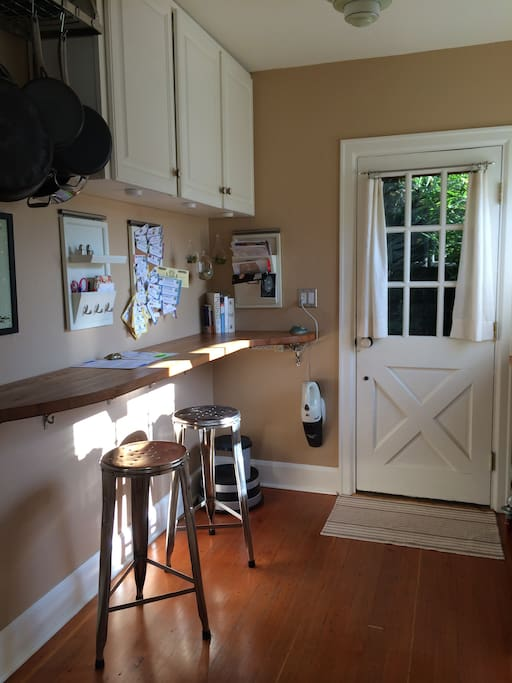 Kitchen with bar and door that also accesses a back path to yard