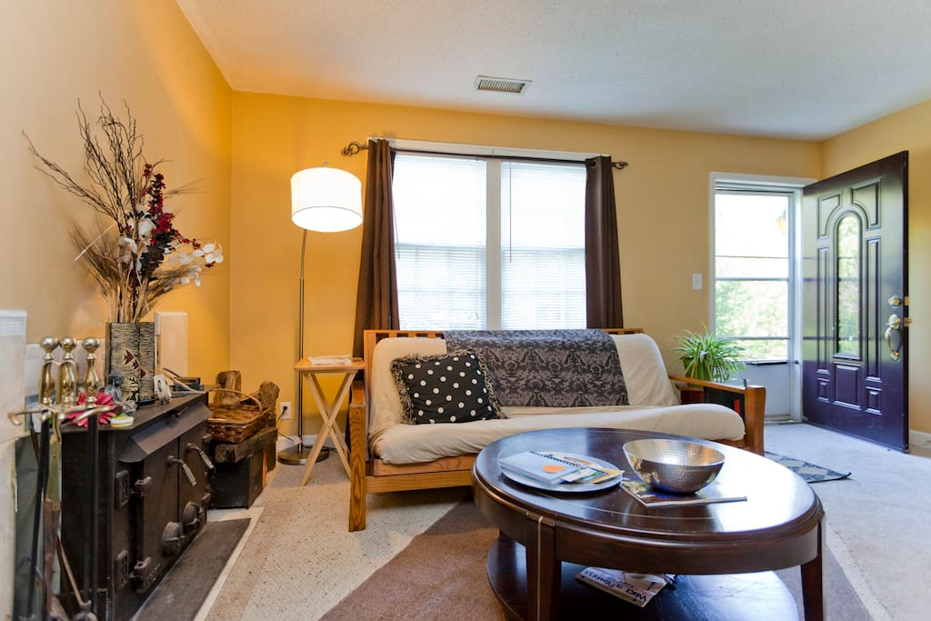 Warm living room with fireplace, sunny windows, guitars and yoga mats in the common area!