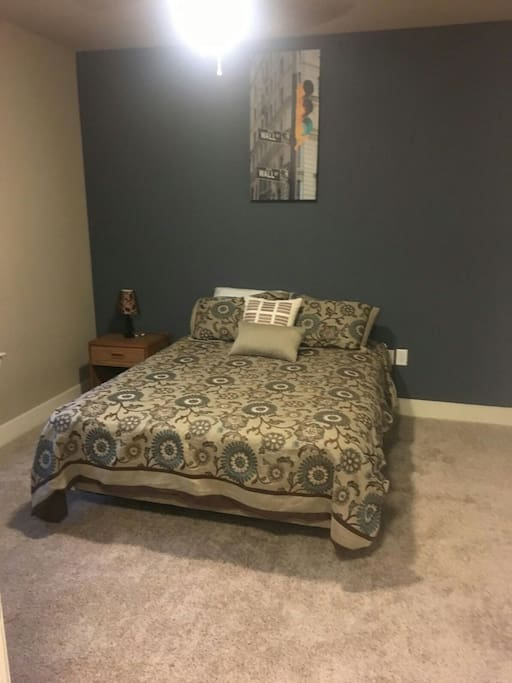 modest bedroom, wall art,  nightstand, lamp, walk-in closet, and iron.
