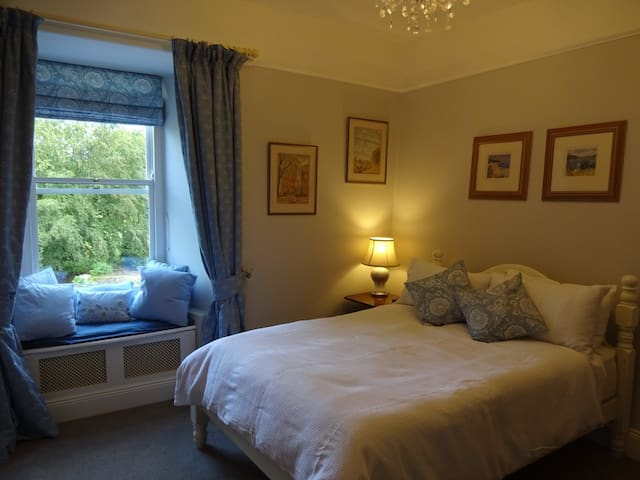 Bright airy bedroom with views over the garden and river
