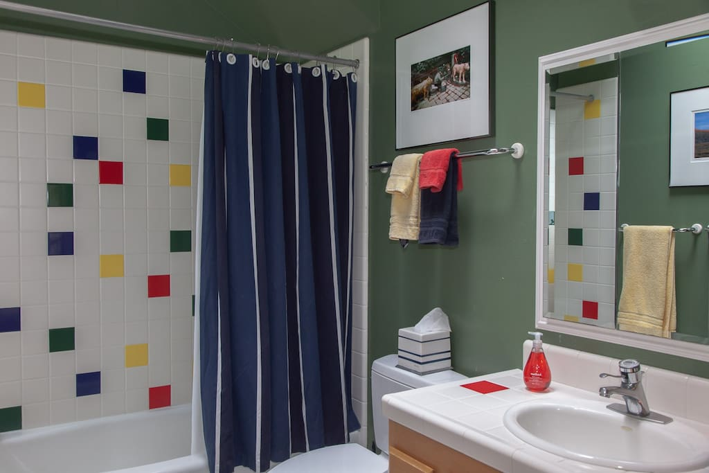 The upstairs bathroom has a colorful tiled shower and tub; hairdryer is available.
