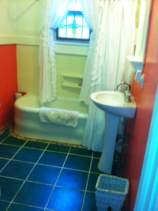 Original 1927 ceramic tub and newer ceramic and tumbled marble tiles.