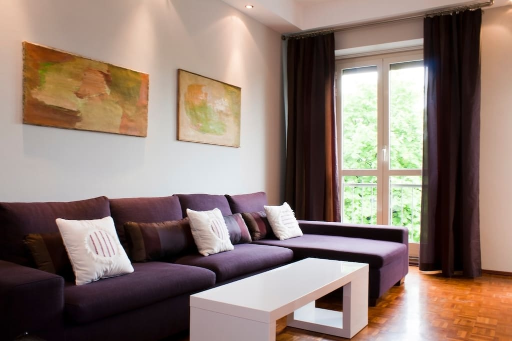 The large modern couch with a view of the garden outside