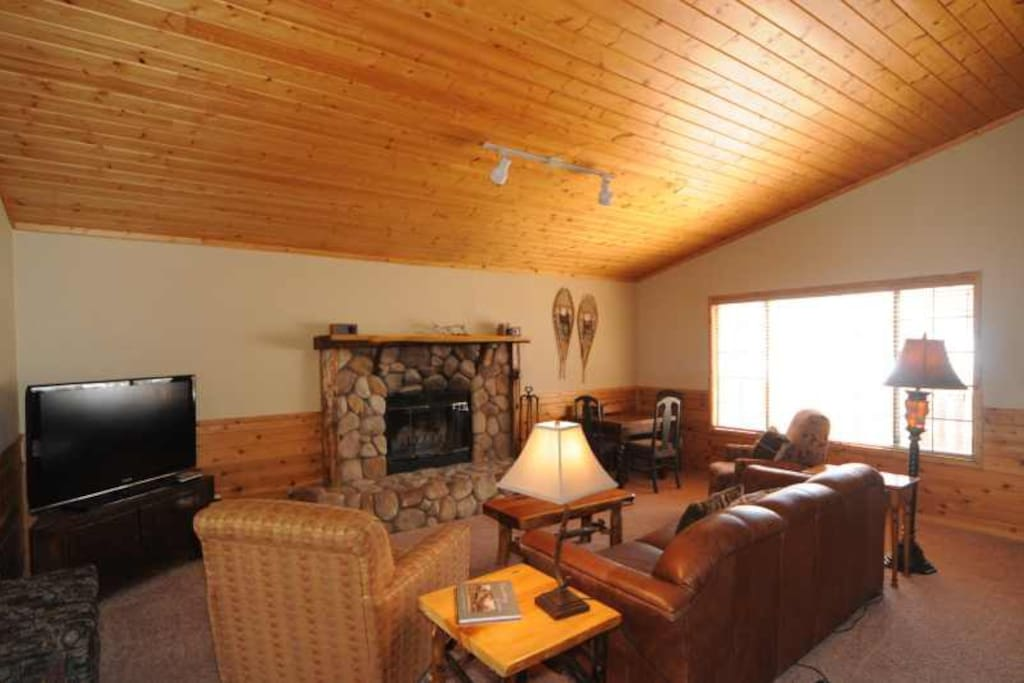 Living room with fire place, TV, game table.