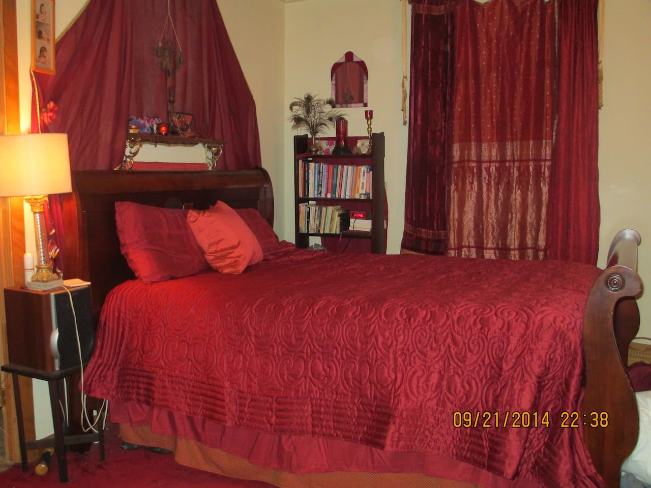 Red master bedroom with queen bed and cathedral ceiling.