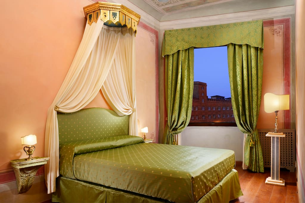 A comfortable and thick mattress (queen bed) along with high quality bed linen, noise reducing windows, shutters and curtains to enjoy a good night's sleep. Antique canopy crown, original old mural paintings and a magnificent view of Piazza del Campo from the bedroom, will make you feel in your honeymoon