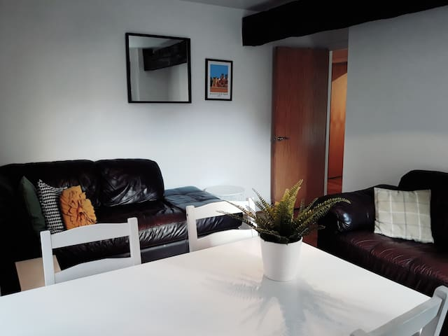 Modern & bright living/dining area with 2 large comfy sofas ready to sink into after a long days sightseeing!