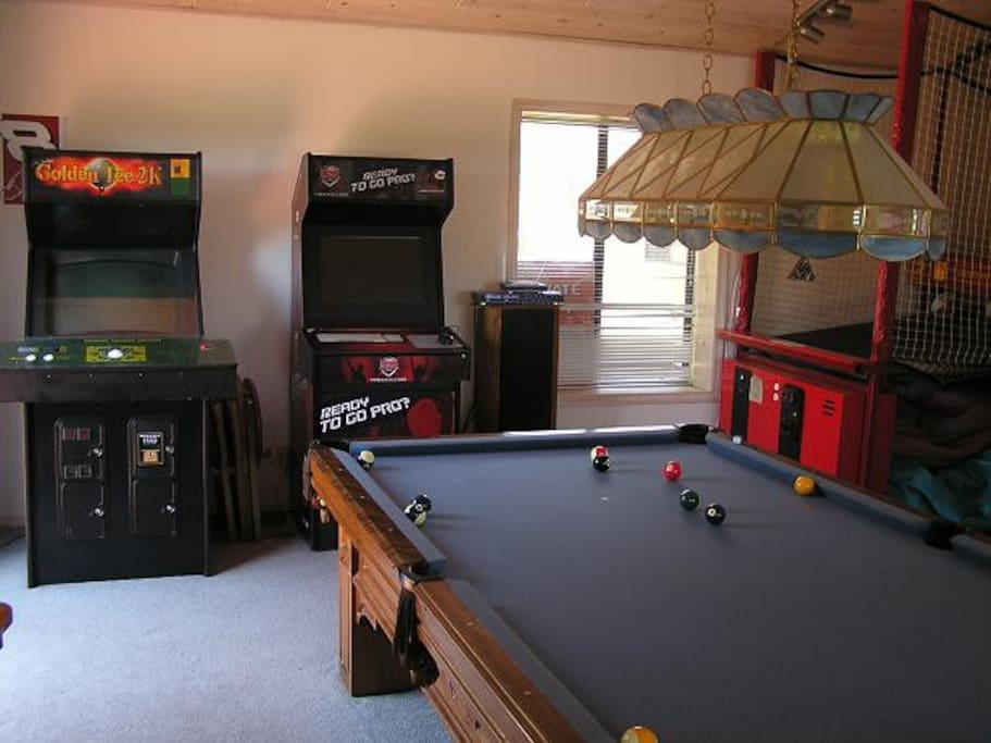 Game room with 9-ft pool table, basketball and golf arcade games and custom gaming console with sound system.