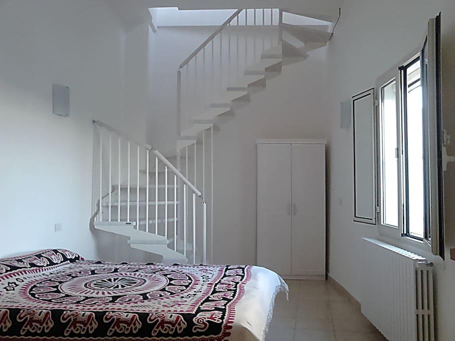 Camera matrimoniale con bagno annesso e le scale che portano al vano + terrazzo