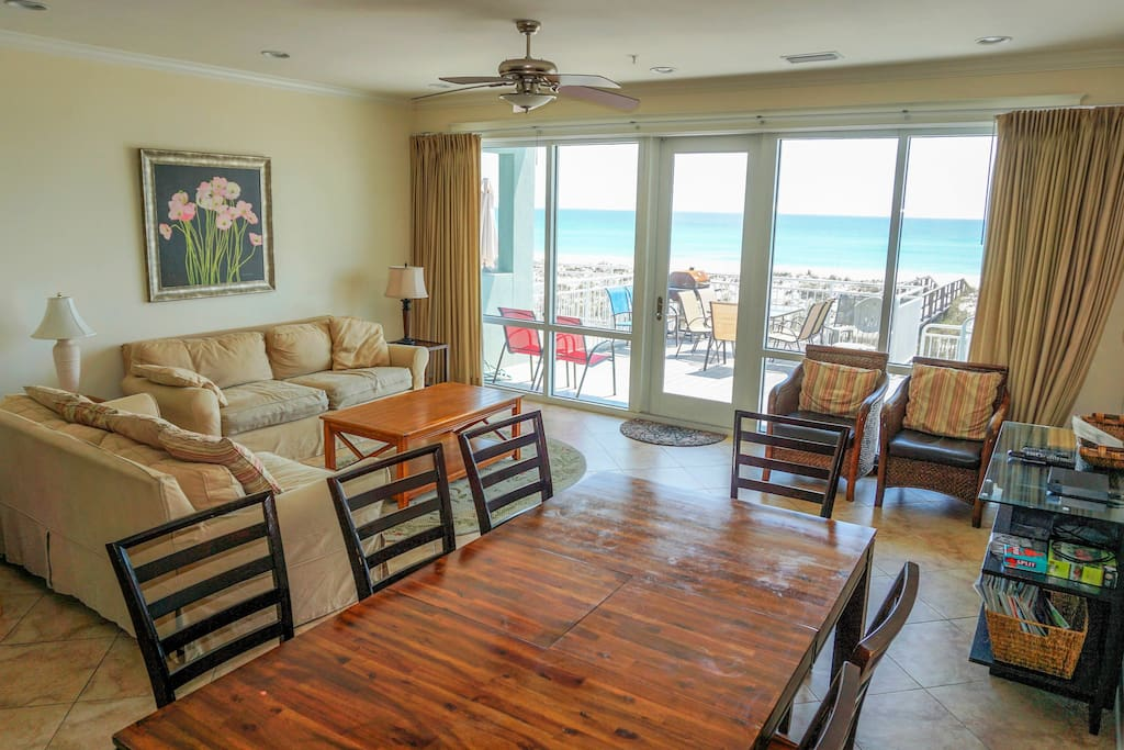 Dining area and living area with access to deck with steps leading to sugar white sand beach
