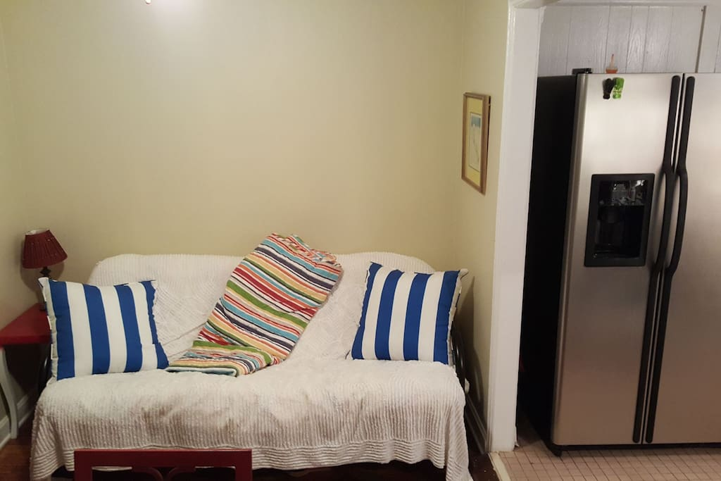 Futon adjacent to kitchen folds down into another bed.