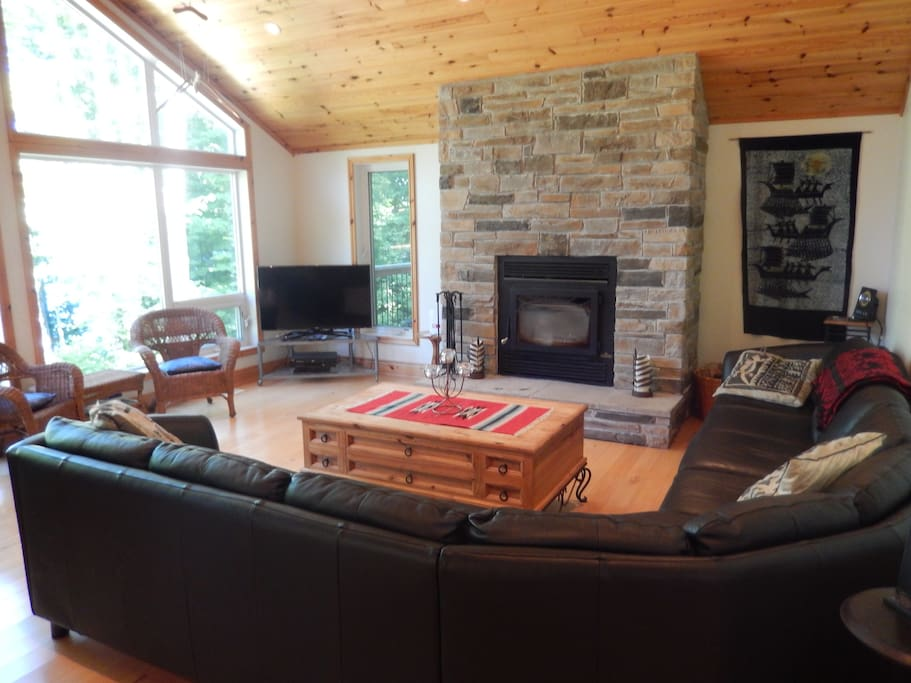 Living room with luxury 8 seater leather sofa, fireplace, HDTV and view to lake