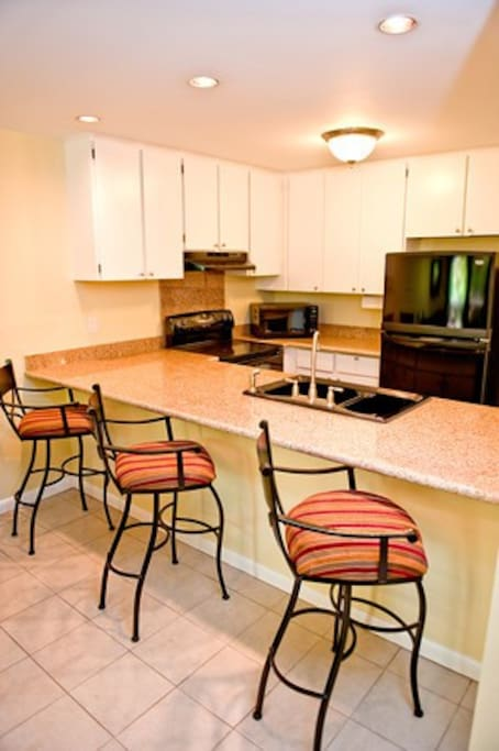 Barstools overlook new granite counter and remodeled kitchen with all new appliances.