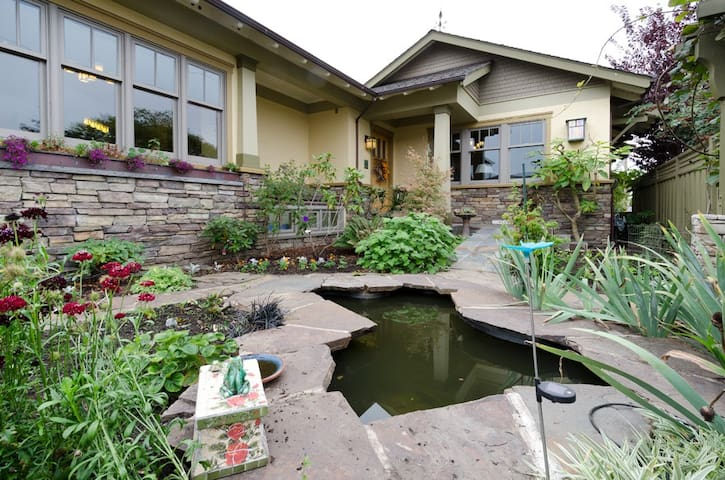 Fishpond at entry, with sunlit patio and cottage garden.