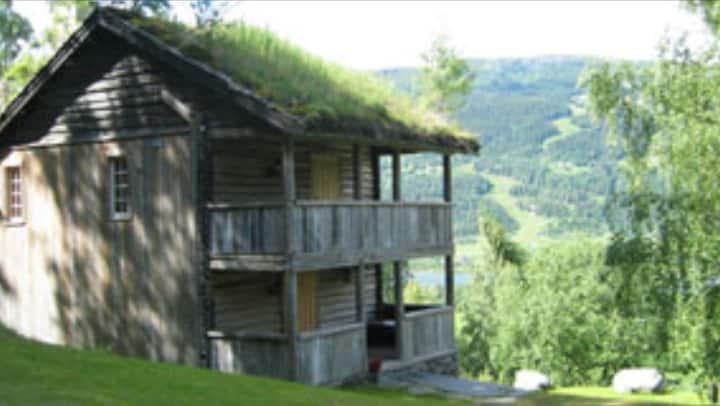 Idyllisk tømmerhus på gårdsbruk.