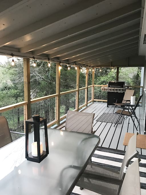 Large covered patio with a grill, lots of seating, and string lights!