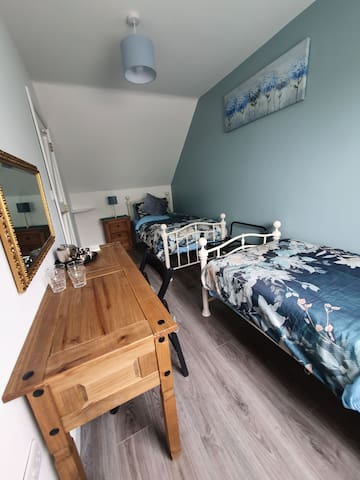 This room has two single beds , dressing table, hanging space. The blinds are blackout to ensure a good night's sleep.