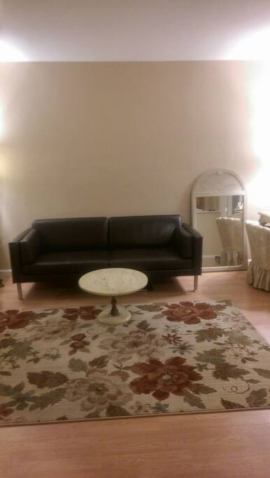 Leather couch, rug, and small marble table