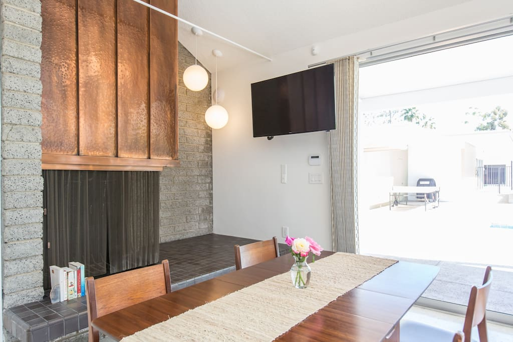 Dinning table and hand hammered fireplace (not in use). Flat screen TV is on extending arm.