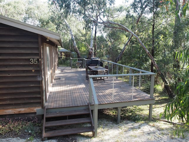 The deck surrounded by trees.  Take a break here after a day at the beach.
