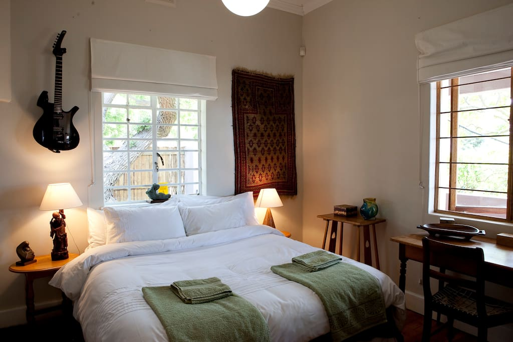 Second bedroom with beautiful light from windows, views on two sides to beautiful lush garden and koi pond.