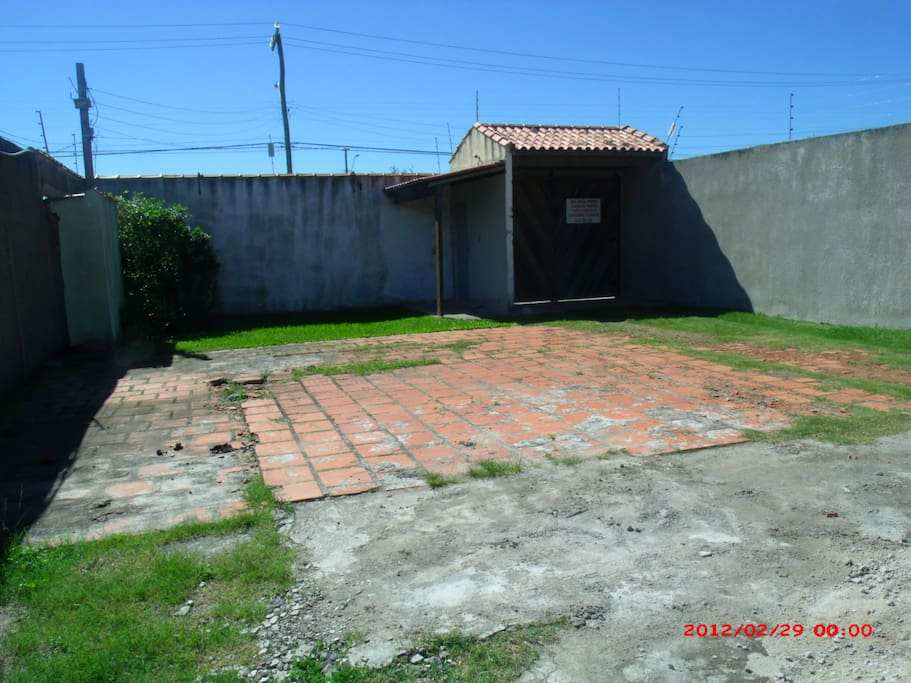 Foto tirada do estacionamento, com vista do portão de entrada.