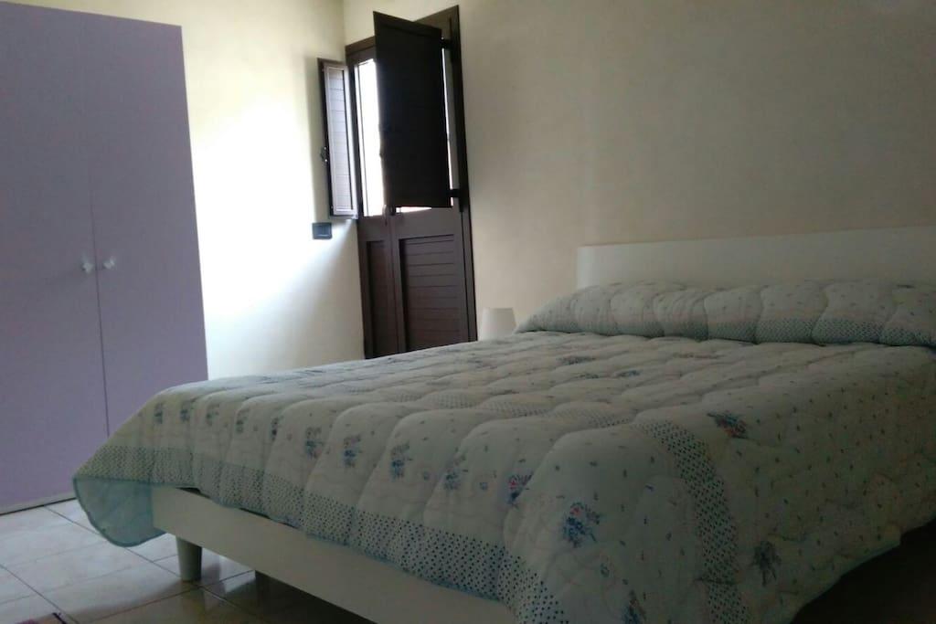 Camera da letto con accesso ad un ampio terrazzo.