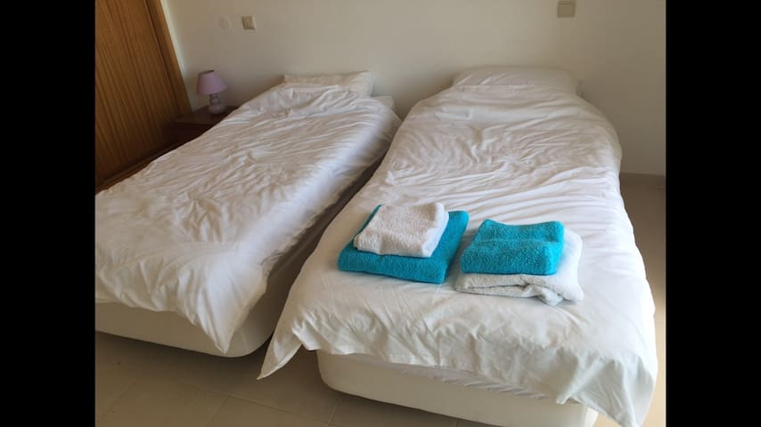 Two single beds in the 2nd bedroom with large wardrobes and patio doors to a large balcony overlooking the pool and countryside.