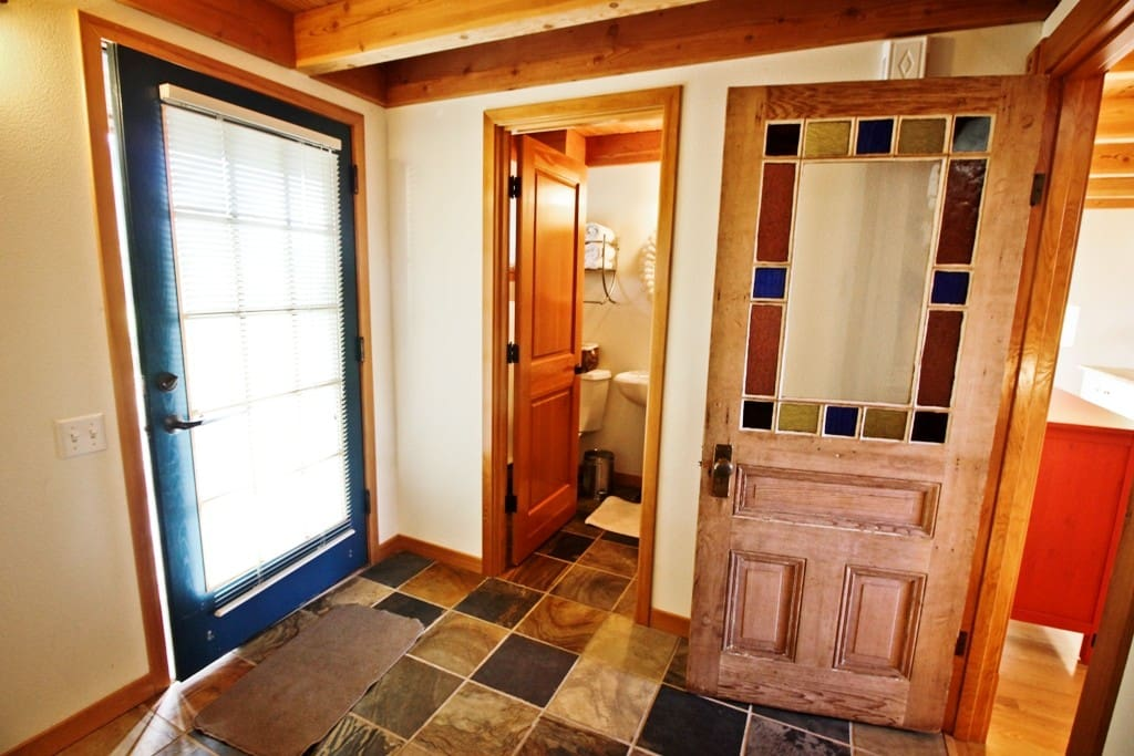 Middle entry level large tiled entry with a coat closet, bench for easy shoe removal and a full bathroom with a sit down shower and pedestal sink