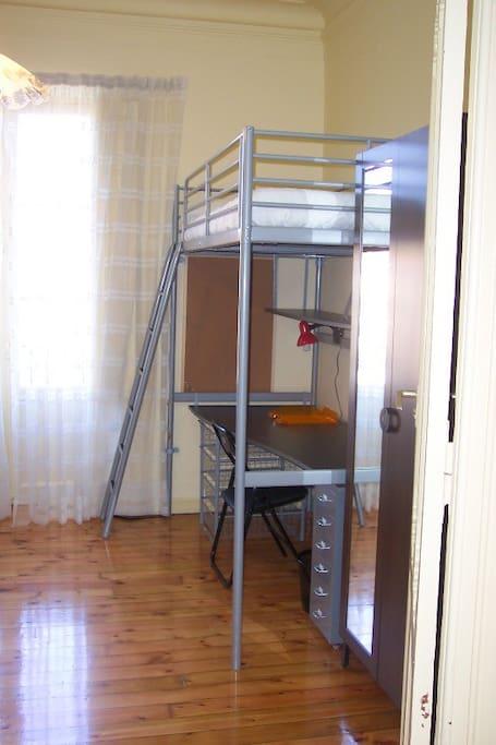 Foto de la misma habitación. Cama elevada a 2 ms. de altura, bajo la cual se coloca otra cama, en San Fermín.