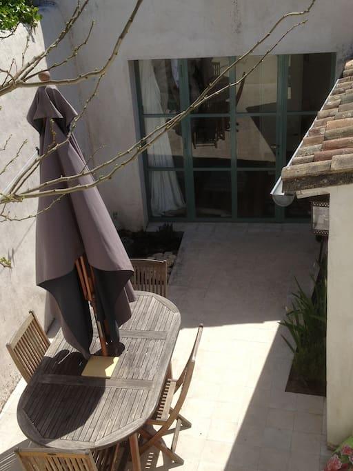 Cour intérieure avec salon de jardin et chaises longues
