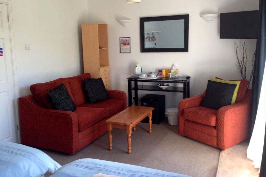 Lovely lounge area in room, with sofa, chair and TV. Kettle, with coffee and tea, and mini-fridge in room.