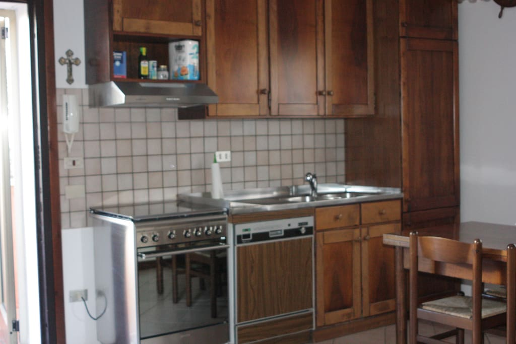 Cucina lato nord: forno elettrico e piano cottura, lavastoviglie, lavello, frigorifero e dispensa