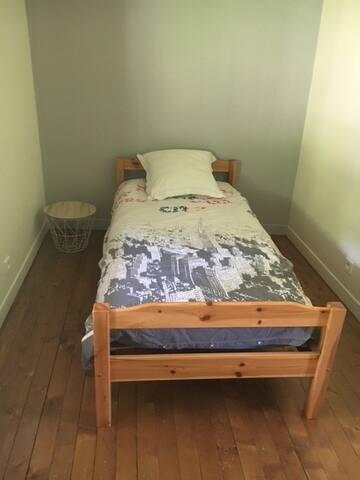 chambre avec lit simple qui dispose d'un placard. sol en parquet bois massif