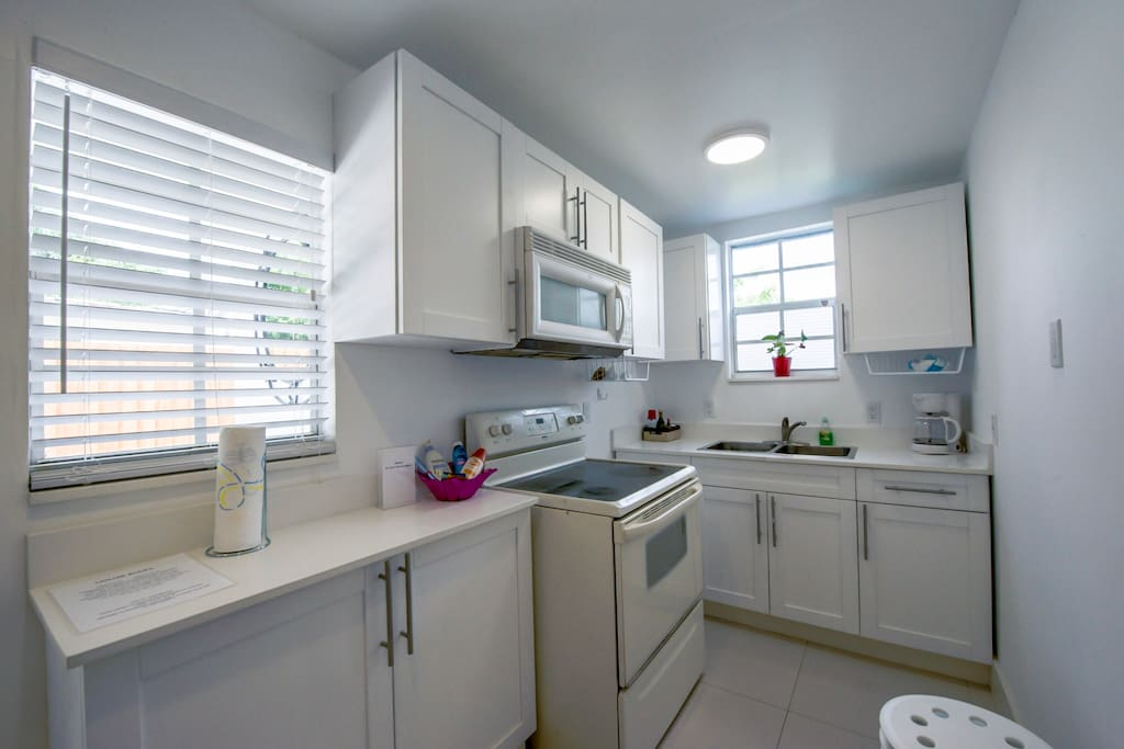 Small kitchen, sink, microwave, stovetop.